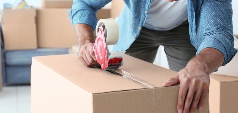 Closeup of man packing cardboard box